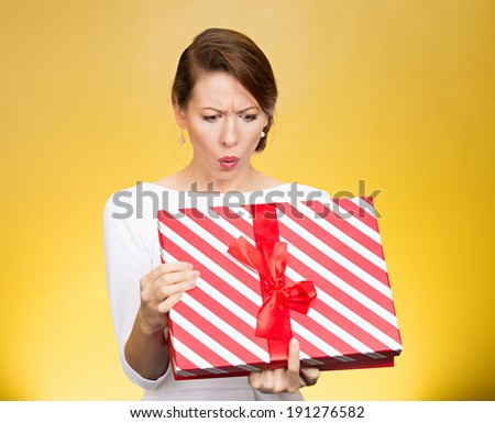 Closeup portrait young funny woman holding opening gift box, surprised, shocked with unexpected present received, isolated yellow background. Sudden human emotion, facial expression, feeling, reaction