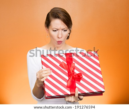 Closeup portrait young funny woman holding opening gift box, surprised, shocked with unexpected present received, isolated orange background. Sudden human emotion, facial expression, feeling, reaction