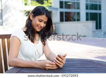 Closeup portrait, young happy business woman in white dress sitting, checking her cellphone, isolated on background of building, chair and table, on a sunny summer day. Business communication