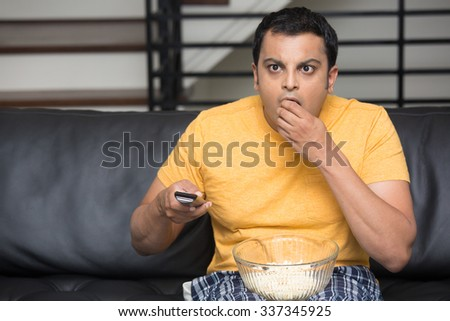 Closeup portrait, young man in yellow t-shirt, sitting on black leather couch, watching TV, holding remote, surprised at what he sees, munching popcorn, isolated indoors flat background