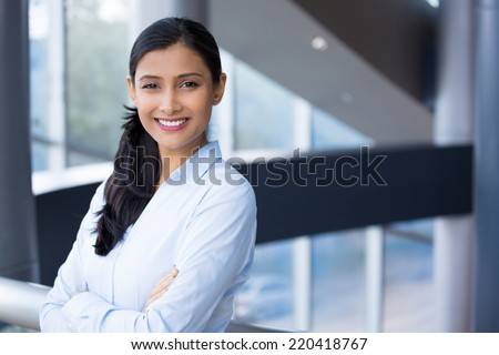 Closeup portrait, young professional, beautiful confident woman in blue shirt, arms crossed folded, smiling isolated indoors office background. Positive human emotions