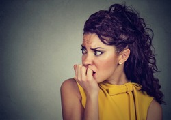 Closeup portrait young scared nervous woman biting her fingernails craving for something or anxious isolated on gray background. Negative human facial expression feeling