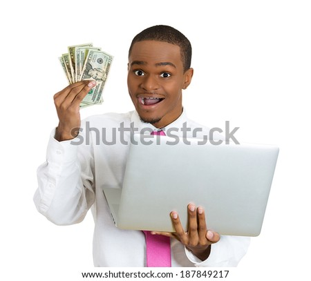 Closeup portrait, young successful business man making money from internet at home, holding cash in hand, laptop in another, isolated white background. Positive human emotion facial expression feeling