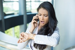 Closeup portrait, young woman in gray business suit blazer talking on cell phone concerned about running out of time on watch, isolated indoors office background