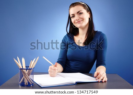 Closeup pose of a happy young student sitting at her desk with a notebook in front, on blue background - stock photo