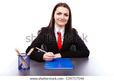 Closeup pose of a young businesswoman sitting at her desktop with a notebook in front of her