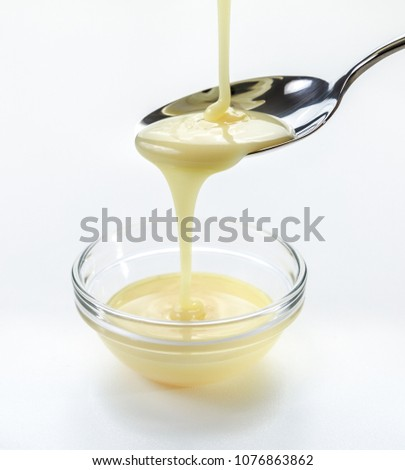 closeup pouring condensed milk with teaspoon on white background
