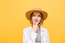 Closeup pretty pensive woman in light clothing on yellow background, isolated on yellow background, looking aside with pensive positive face and hand on beard.Thoughtful girl on a yellow background