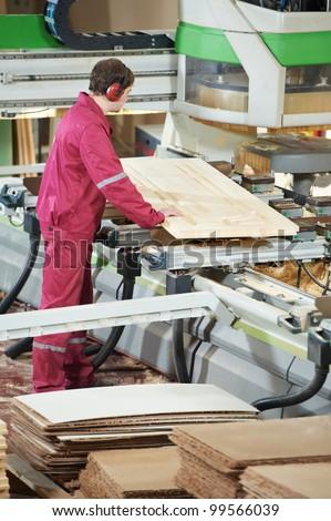 Closeup process of carpenter worker with circular saw machine at wood beam cross cutting during furniture manufacture