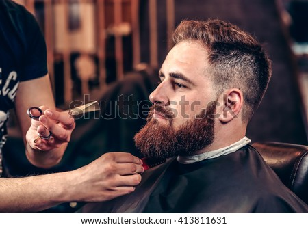 Closeup professional grooming beard with scissors in a Barbershop. Portrait of a bearded man hipster in a Barbershop during haircut. Stylish man hair cut at the barber shop.