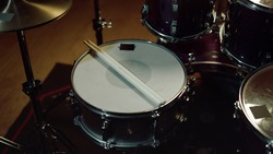 Closeup professional musical instrument. Drum kit for jazz band in recording studio. Drumsticks lying on drum. Drum set with drum cymbals.