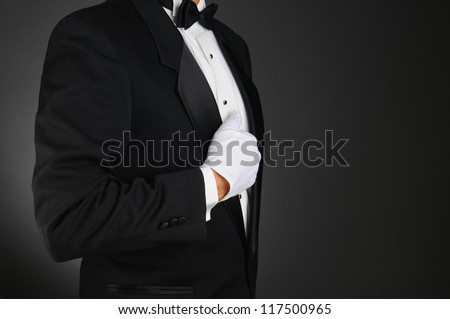 Closeup profile of a man wearing a tuxedo and white gloves holding his lapel. Horizontal format on a light to dark gray background. Man is unrecognizable.