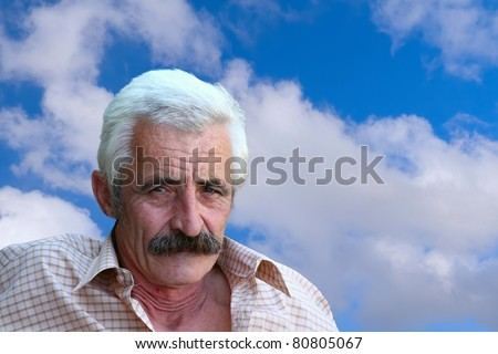 Closeup Profile on a good looking Old Man and blue sky with clouds in the background
