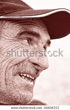 Closeup Profile on a Smiling Old Man With a Cap on Head