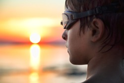 Closeup Profile Portrait Of Boy With Swimming Goggles Looking At The Sun, Twilight Blur Background