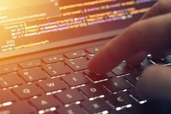 Closeup programmer coding on screen. Hands coding html and programming on laptop screen, web development, developer