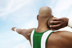 Closeup rear view of a shot putter preparing to toss shot put against the sky