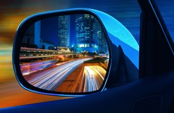 Closeup rearview mirror car at full speed at night in big modern  metropolis with skyscrapers