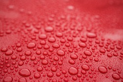 Closeup red car paint surface with hydrophobic ceramic coating