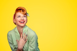 Closeup red head young excited woman pretty pinup girl green button shirt smiling laughing looking up isolated on yellow background retro vintage 50's style. Human emotions body language positive face