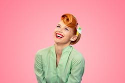 Closeup red head young woman pretty pinup girl green button shirt laughing smiling looking up isolated on pink background retro vintage 50's style. Human emotions body language