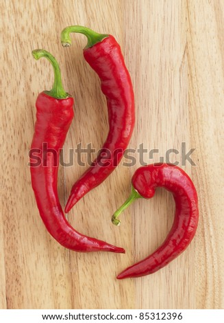 Closeup red hot peppers on wood board