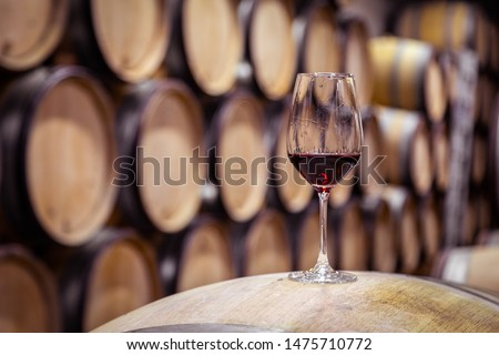 Closeup red wine glass on background of wooden oak barrels stacked in straight rows in order in cellar of winery, vault. Concept professional degustation, winelover, sommelier travel Foto stock ©