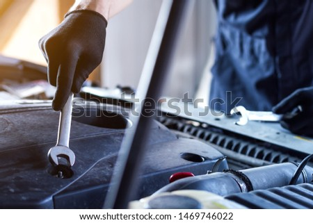 Closeup repairman hands are holding metal wrenches. Open hood with automobile motor on background. Repairer is repairing car at service station garage. Tool for mechanic at auto repair shop. #1469746022