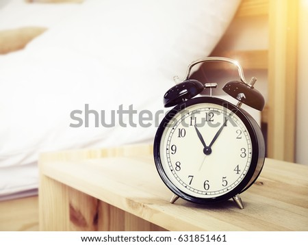 Closeup retro alarm clock on Bedside table with bed background and copy space, retro style #631851461
