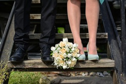 Closeup retro and vintage portrait of beautiful wedding bouquet placed next to groom's and bride's feet, standing on stairs of train locomotive.