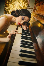 Closeup retro portrait young beautiful cute woman finger wave hairstyle. creative holiday makeup smokey cat eyes red lips. musician plays piano melody touches keys her hand. gold dress old style 1920s