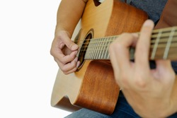 Closeup right hand of someone playing guitar on white background