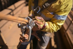 Closeup rope access industry worker hand wearing full body safety harness, using secondary safety backup device static twin ropes abseiling, descending from construction mine site, high rise building