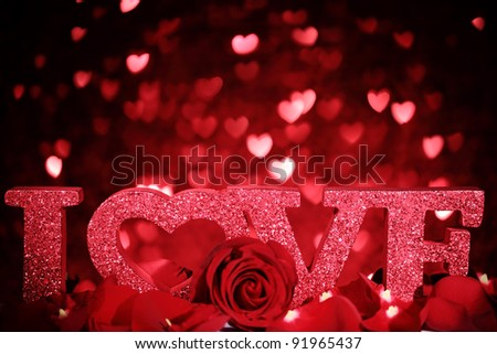 Closeup roses and LOVE symbol on hearts background.Romantic traditions.