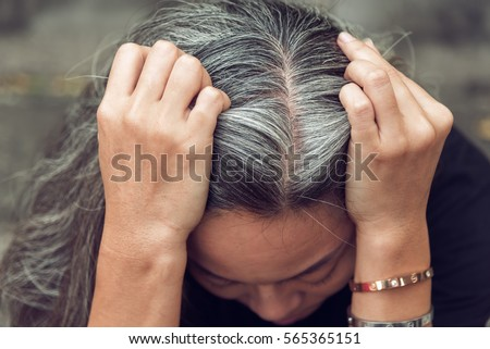 Closeup sad asian young beautiful woman and gray hair with worried stressed face expression looking down ストックフォト ©