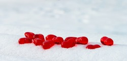 Closeup set of small bright red glass hearts on powdery snow of snowdrift at cold winter day, symbol of romantic love, St. Valentine's Day holiday concept, low angle shoot