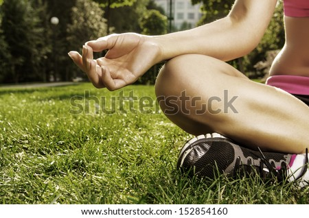 Closeup shoot. Hand of young caucasian woman sitting in lotus pose in the park