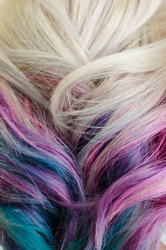 Closeup shoot of female head with fresh dyeing colorful unicorn or rainbow hair.