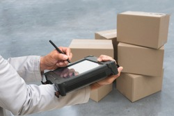Closeup shooting hand of QC. worker with Rugged computers tablet and Bluetooth barcode scanner checking for logistics, Goods package boxes in warehouse.