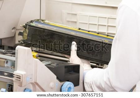 closeup shot hands of technician fixing broken photocopier machine