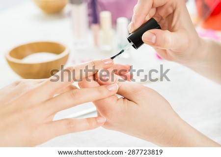 Closeup shot of a beautician applying nail polish to female nails. Woman getting nail manicure. Shallow depth of field with focus on nail polish.