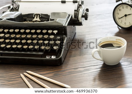 Closeup shot of a desk with a vintage typewriter, cup of coffee, pencils and a clock