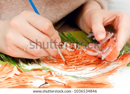 Closeup shot of a girl painting by numbers #1036534846