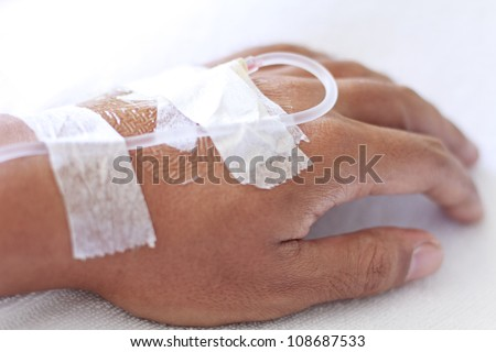 closeup shot of a patient's hand with saline intravenous (iv) - stock photo