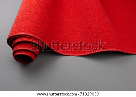 Closeup shot of a red carpet being rolled up, includes space for copy