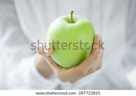 Closeup shot of a woman holding healthy green apple. Girl with a green apple in hands. Shallow depth of field with focus on the green apple.
