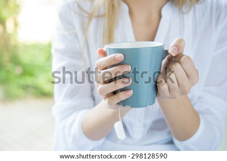 Closeup shot of a woman holding tea mug. Close up of young woman\'s hand holding a cup of hot tea. Relaxed girl drinking tea. Shallow depth of field with focus on tea mug.