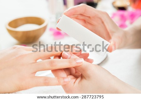 Closeup shot of a woman in a nail salon receiving a manicure by a beautician at nail salon. Woman using a buffer for file nail. Shallow depth of field with focus on nailfile.