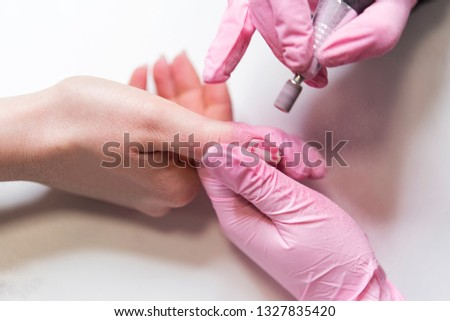 Closeup shot of a woman in a nail salon receiving a manicure by a beautician with nail file. Woman getting nail manicure. Beautician file nails to a customer #1327835420