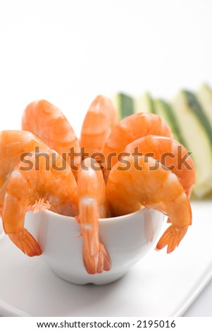 Closeup shot of an appetizer platter, with shrimps in a cup garnished with sliced zucchinis (shallow DOF)